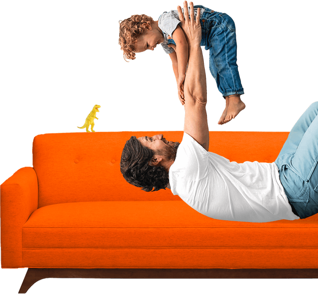 Man on a bright-colored sofa lifting a young child overhead